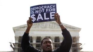 Un homme brandit une pancarte lors d'une manifestation contre l'argent en politique, devant la Cour suprême de Washington, le 8 octobre 2013.
