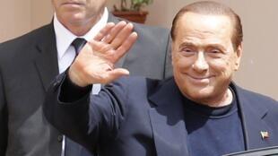 Berlusconi acena ao deixar o centro geriátrico onde iniciou trabalho comunitário em lugar da pena de prisão domiciliar.
