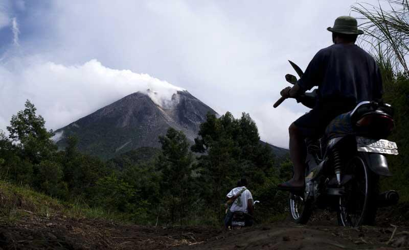 Villagers ride in motorcycles while Mount Merapi volcano emitting smoke is seen from Cangkringan village