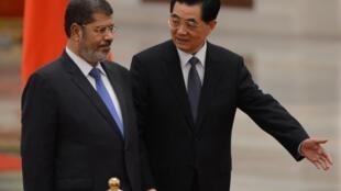 Le président chinois Hu Jintao (D) montre le chemin vers le président égyptien Mohamed Morsi au cours d'une cérémonie de bienvenue à Pékin, le 28 août 2012.