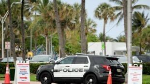 Un véhicule de police est stationnée près du bord de mer à Miami, le 5 avri 2020.