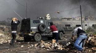 Palestinian protesters throw rocks at an Israeli border police vehicle in the West Bank village of Kfar Kadum, 25 January