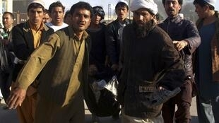 Afghans carry body of injured man after attack on UN compound in Mazar-i-Sharif