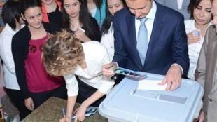 Syrian President Bashar al-Assad (C) votes with his wife Asma