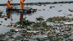 Agentes fazem a limpeza do rio Meriti, em Duque de Caxias, que deságua na Baía de Guanabara.