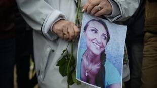 En la multitud reunida para recordar a Julie Douib, una mujer lleva una rosa y una fotografía de esta joven madre de dos hijos que fue asesinada por su expareja en Córcega en marzo de 2019.