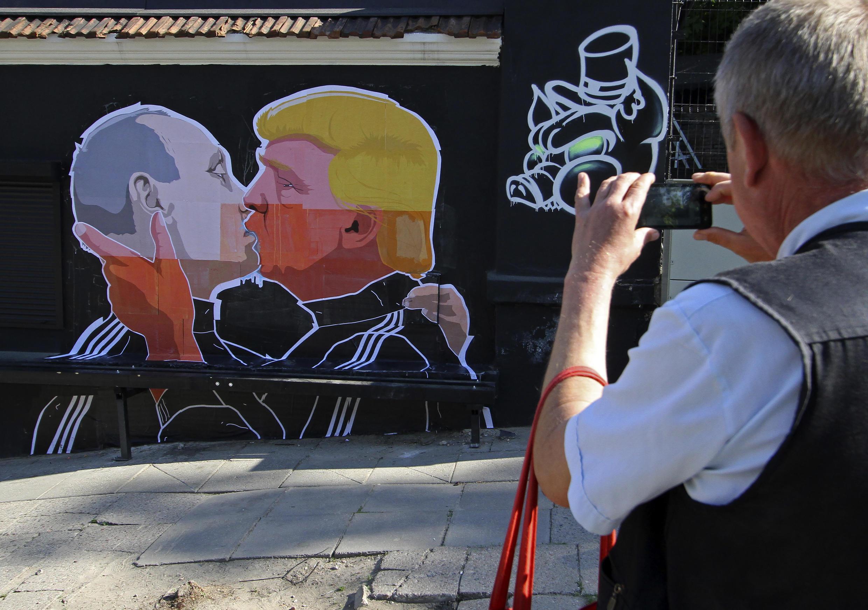 Một người đàn ông đang chụp một bức tranh trên tường của một nhà hàng vẽ cảnh Donald Trump và ông Vladimir Putin đang hôn nhau, ngày 13/05/2016.