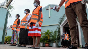 Church members wait for believers to measure their body temperature during a Palm Sunday mass at the Full Gospel Bible Fellowship Church in Dar es Salaam, Tanzania, on 5 April 2020.