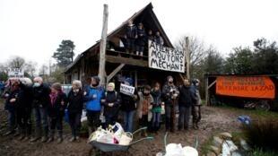 """Manifestantes formam uma linha perto de uma casa com a mensagem """"Atenção, ovelhas malvadas"""" durante uma operação de evacuação por policiais franceses em Notre-Dame-des-Landes"""