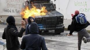 Unos jóvenes atacan un vehículo policial en Valparaíso, Chile, el 9 de agosto de 2011.