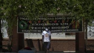 """Un temporero delante de un cartel que reza """"Todas las personas somos iguales"""" frente a la alcaldía de Lepe, cerca de Huelva, el 29 de julio de 2020, durante una protesta contra sus precarias condiciones de vida."""