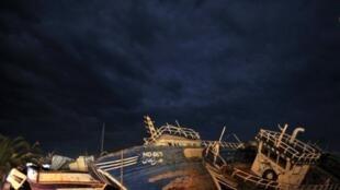 Carcasses de navires utilisés par les migrants restent échouées sur la côte de l'île de Lampedusa.