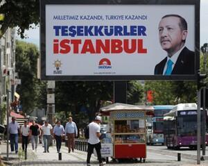 People walk past a poster for Turkey's President Tayyip Erdogan in Istanbul, Turkey, June 25, 2018.
