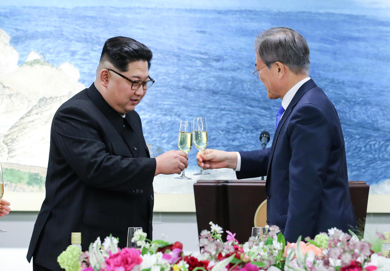 Presidente sul-coreano Moon Jae-in (dir.) e o l1der norte-coreano Kim Jong-un, celebram acordo militar, em Panmunjeon, na zona desmilitarizada entre as duas Coreias, a 27 de abril de 2018.