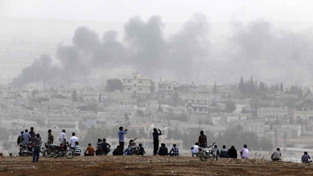 Raia wa Kikudi wakiangalia ndege za kivita zikiwa kwenye anga ya mji wa Kobane.