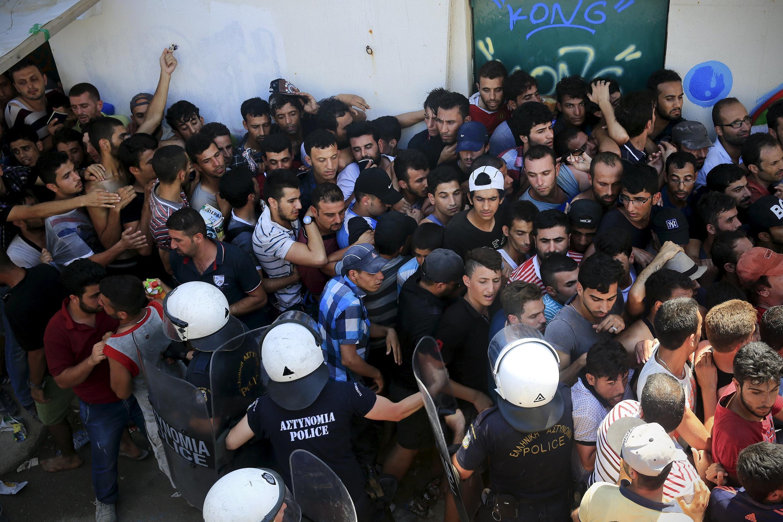 Migrants et réfugiés se pressent à l'entrée du stade pour être enregistrés afin d'obtenir un laissez-passer pour poursuivre leur voyage vers Athènes et d'autres pays européens. Kos, le 12 août 2015.