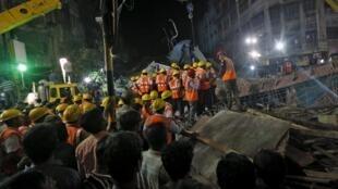 Equipes de segurança buscam vítimas entre as estruturas que ruíram.