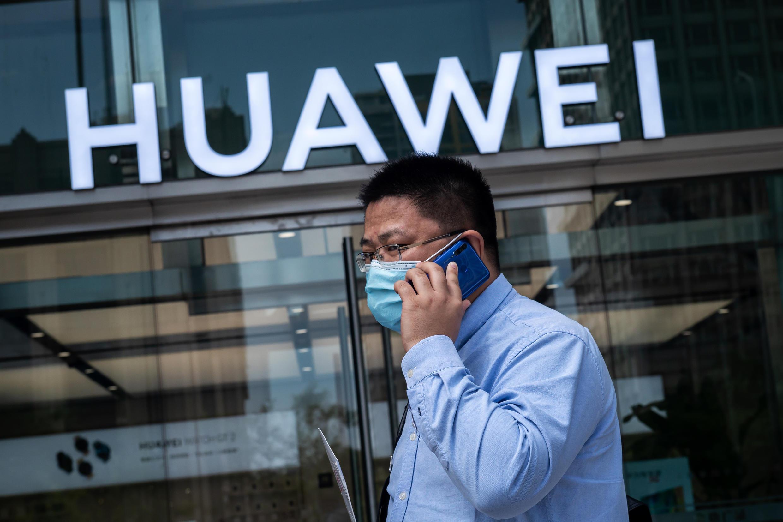 Un hombre habla por teléfono mientras pasa frente a una tienda de Huawei el 25 de marzo de 2020 en Pekín