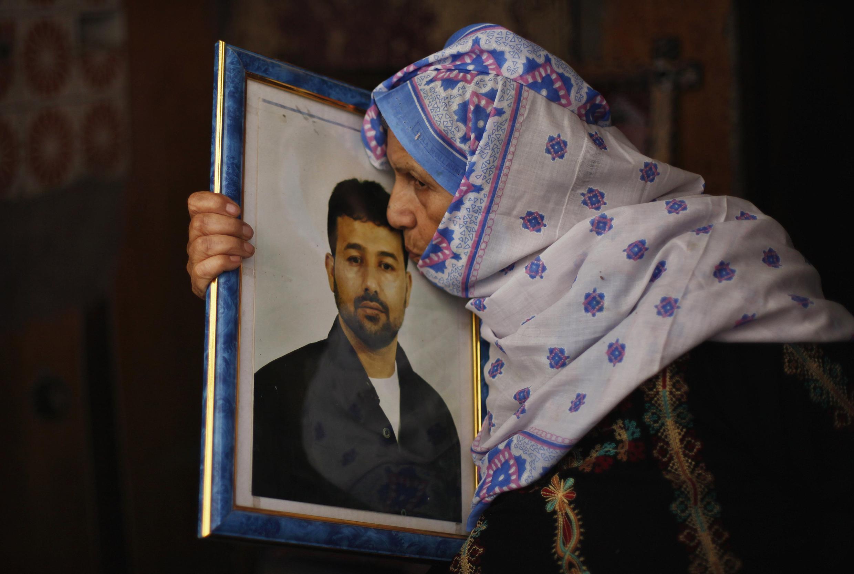 La mère d'un prisonnier palestinien embrasse le portrait de celui-ci à l'annonce de sa libération, le 12 août 2013.