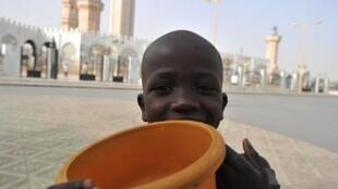 Wani almajiri dauke da kwanon baransa a kusa da babban Masallacin Touba a kasar Senegal