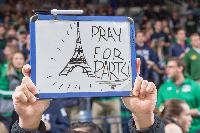 A South Bend dans l'Indiana, un étudiant brandit un panneau en solidarité avec Paris avant un match de basketball.