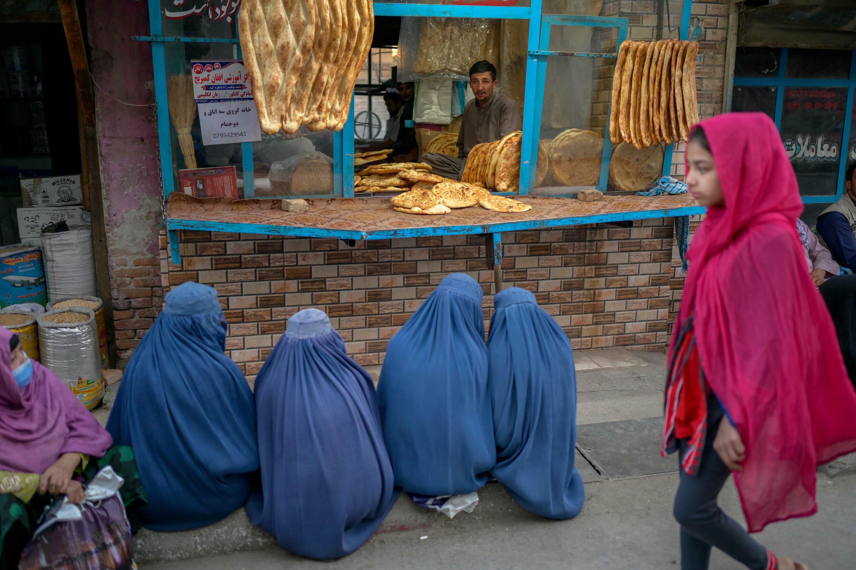 Mujeres vistiendo una burka, esperan frente a una panadería en Kabul, el 16 de septiembre de 2021