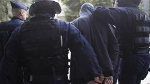 Polícia francesa escolta jovem detido para interrogatório após onda de violência no bairro de Villeneuve, em Grenoble.