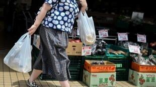 Una mujer sale con dos bolsas de plástico tras comprar en un supermercado de Tokio el 24 de junio de 2020