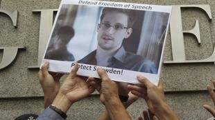 Protesters in support of Edward Snowden hold a photo of him during a demonstration outside the US. Consulate in Hong Kong