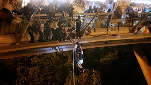Anti-government protesters trapped inside Hong Kong Polytechnic University abseil onto a highway and escape before being forced to surrender during a police besiege of the campus in Hong Kong, 18 November 2019.