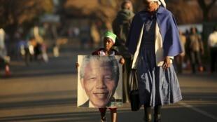 Une petite fille transportant un portrait de Nelson Mandela, non loin de la clinique où il est hospitalisé à Pretoria, le 3 juillet 2013.