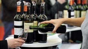 A woman serves a glass of wine during the Independent Winegrowers show in Paris.