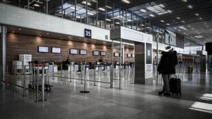 Un hombre aguarda frente a unos mostradores sin pasajerso en una desierta terminal del aeropuerto de Orly, el 30 de marzo de 2020 al sur de París
