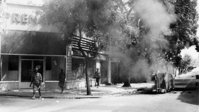 Une voiture brûle au milieu d'une rue lors des violents affrontements entre les forces de l'ordre et les étudiants et ouvriers sénégalais à Dakar le 31 mai 1968.