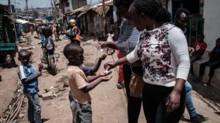 Una voluntaria de una ONG reparte producto desinfectante de manos a niños del suburbio pobre de Kibera como medida de prevención contra el coronavirus, el 18 de marzo de 2020 en Nairobi, la capital keniana