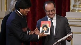 O presidente francês, François Hollande (direita), recebe livro oferecido pelo presidente da Bolívia, Evo Morales, depois de uma reunião no Palácio do Eliseu, em Paris.