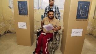 Un homme en fauteuil roulant vient voter, ce merdredi 30 avril à Bagdad.