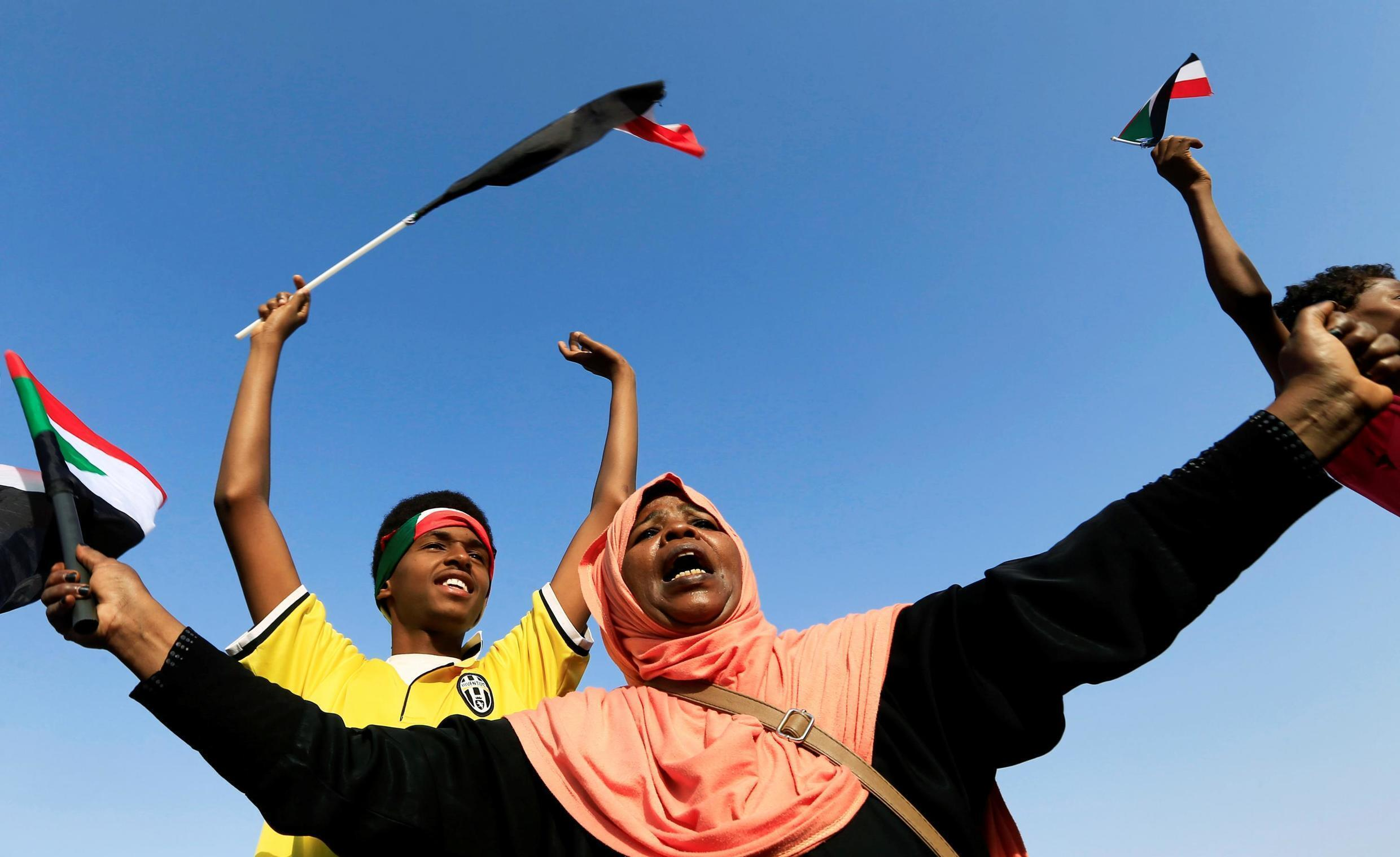 A Sudanese woman chants slogans and wave national flag in celebration, after the ruling military council and a coalition of opposition and protest groups reach a power-sharing agreement, Khartoum, Sudan, July 5, 2019.