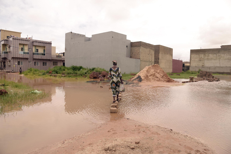 Une femme marche sur des briques placées dans des eaux inondées dans le quartier de Keurs Massar à Dakar le 7 septembre 2020 après de fortes pluies au Sénégal.