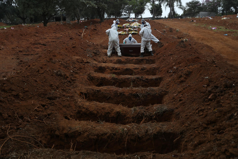 در برزیل تنها در یک روز، ١٤٧٣ تن بر اثر ابتلا به کووید١٩ جان خود را از دست دادند. کارگران گورستان سائوپولو، ٤ ژوئن ٢٠٢٠