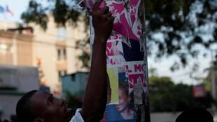 Un manifestant arrache une affiche du candidat à la présidence de PHTK, Jovenel Moise, lors d'une manifestation contre les résultats de l'élection présidentielle à Port-au-Prince, le 16 décembre 2016.