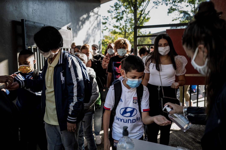Des élèves portant un masque et recevant du gel hydroalcoolique à la rentrée du collège à Bron le 1er septembre 2020.