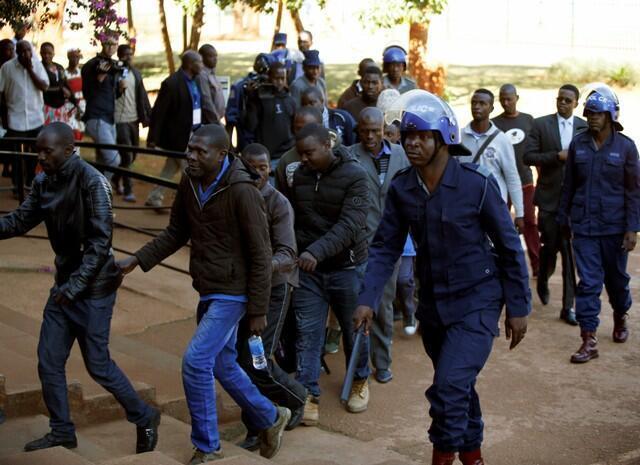 Baadhi ya watu waliokamatwa, baada ya polisi kuzingira makao makuu ya chama upinzani cha MDC, wakifikishwa katika mahakama ya mji mkuu Harare.