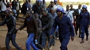 Wasu daga cikin 'yan adawa da jami'an tsaro suka kama a hedikwatar jam'iyyar adawa ta MDC a birnin Harare. 4 ga watan Agsuta, 2018.