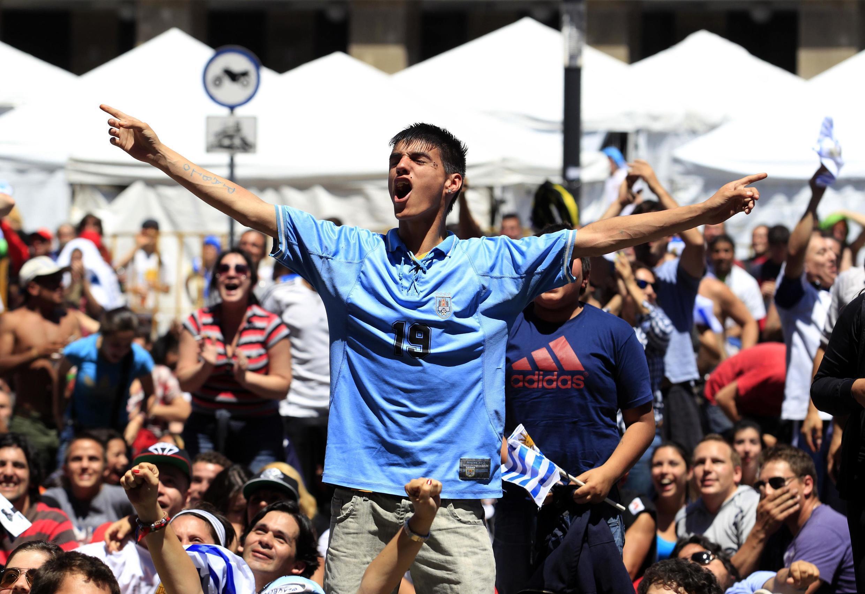 Uruguayos festejan mientras miran el partido en la avenida 18 de julio, en Montevideo.