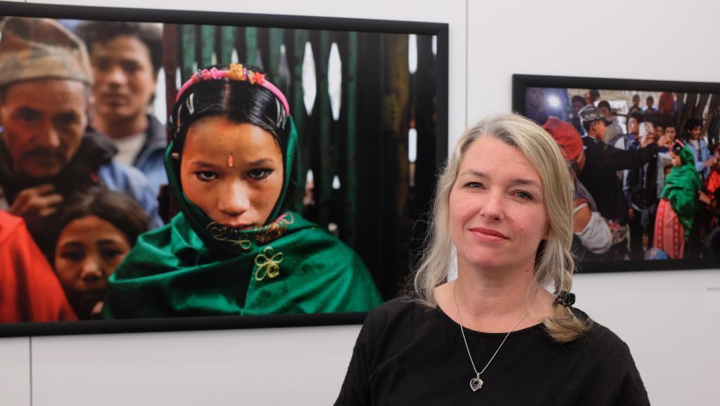 A fotógrafa Stéphanie Sinclair no Nepal, diante da foto de Naruna, 14 anos, no dia do seu casamento