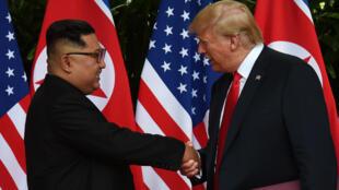 Kim Jong un (trái) và Donald Trump bắt tay nhau sau khi ký kết thông cáo chung, Singapore, ngày 12/06/2018.