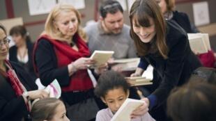 Первая леди Франции Карла Бруни на парижском Книжном салоне 2011 раздает книги юным посетителям. 18/03/2011
