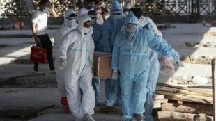 Des soignants et des proches portent le corps d'une victime du Covid-19, pour une crémation. Le 26 avril 2021, à Jammu, en Inde.