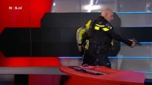 Policial em ação no estúdio da televisão pública NOS para imobilizar o homem (não visto na imagem) que invadiu o local com uma pistola falsa. ;